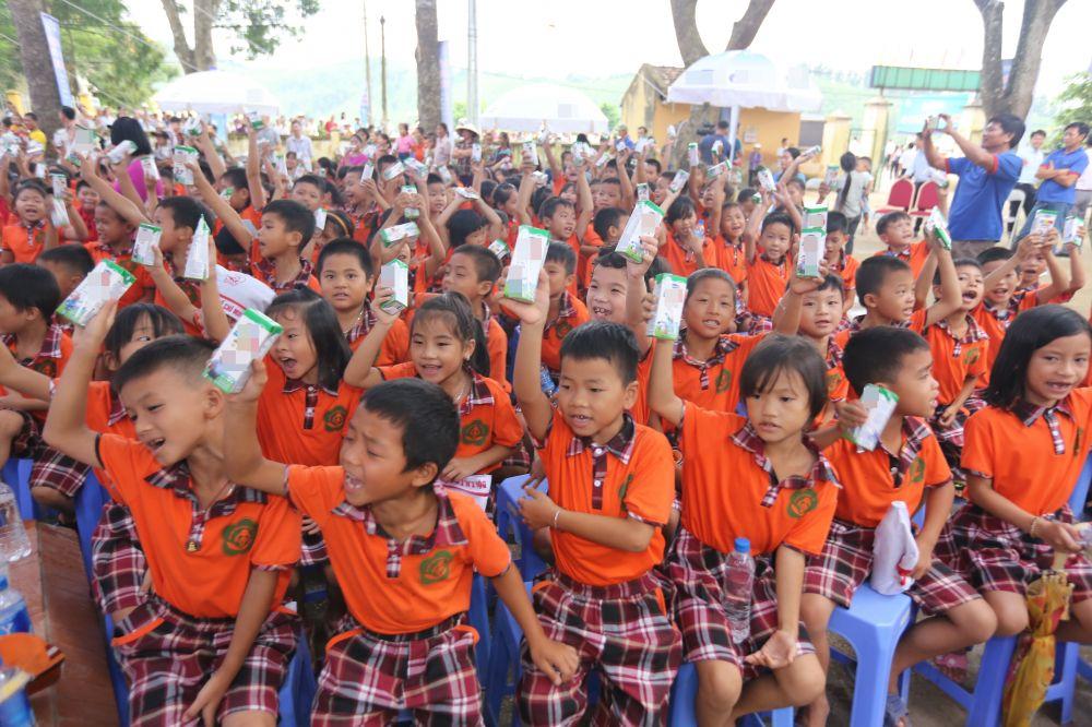 Các em học sinh Việt Nam hào hứng với ly sữa trên tay trong một buổi sinh hoạt tập thể.