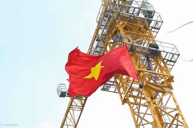 Cờ bay phấp phới trên chiếc cẩu tháp của công trình xây dựng.