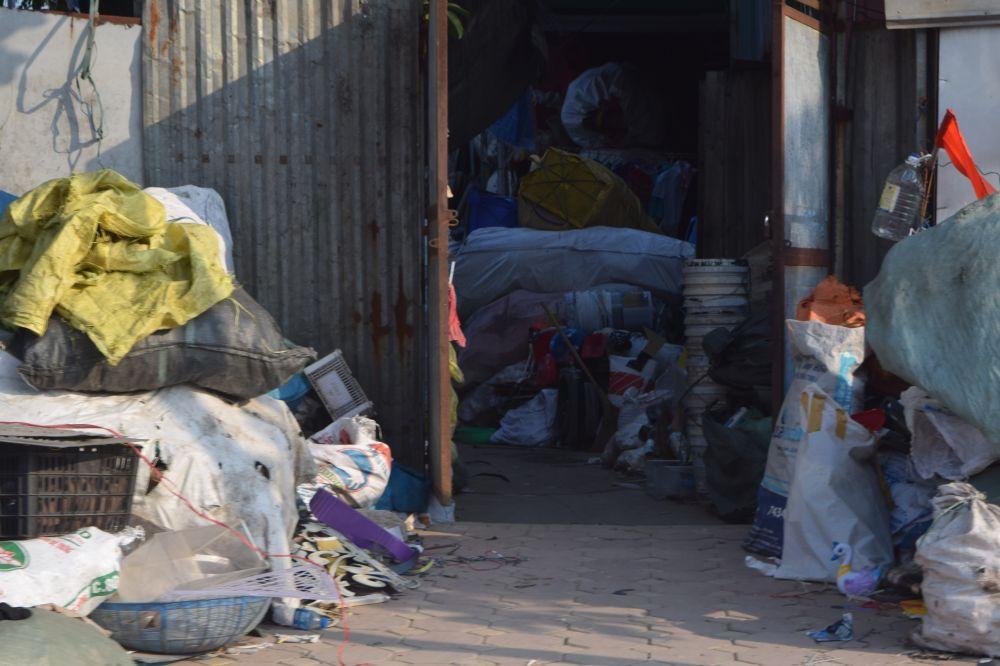 những bao tải nhựa được dựng kín hết cả lối đi lại của một nhà dân