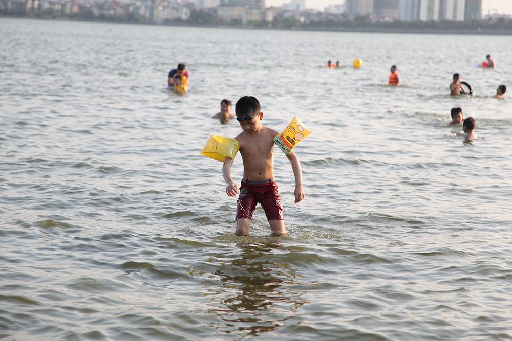 Cậu bé này được trang bị phao bơi đầy đủ nhưng lại dính phải một sợi dây khá dài nằm dưới làn nước Hồ Tây.