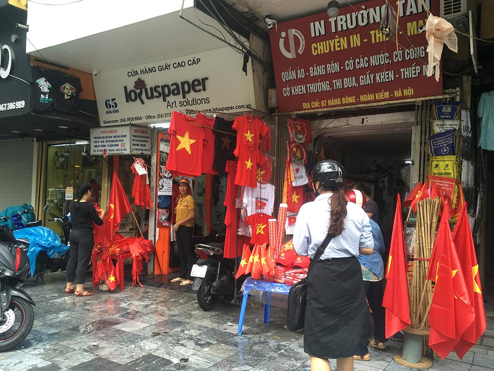 Trước trận đấu, nhiều cửa hàng bán cờ, băng rôn, áo phông thu hút rất nhiều người hâm mộ.