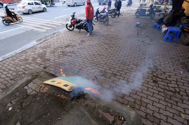 Tại vỉa hè đường Láng, người dân nhặt nhạnh giấy bìa, gỗ vụn để nhóm lửa.