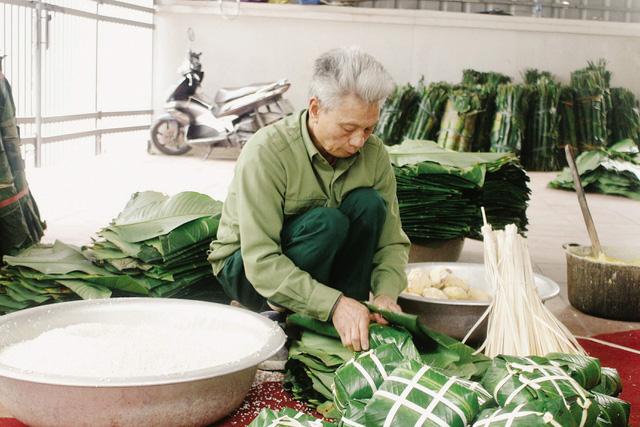 Ông Phạm Văn Bảy (72 tuổi, ở thôn Tranh Khúc) cần mẫn gói từng chiếc bánh chưng. Ảnh: Huyền Trang