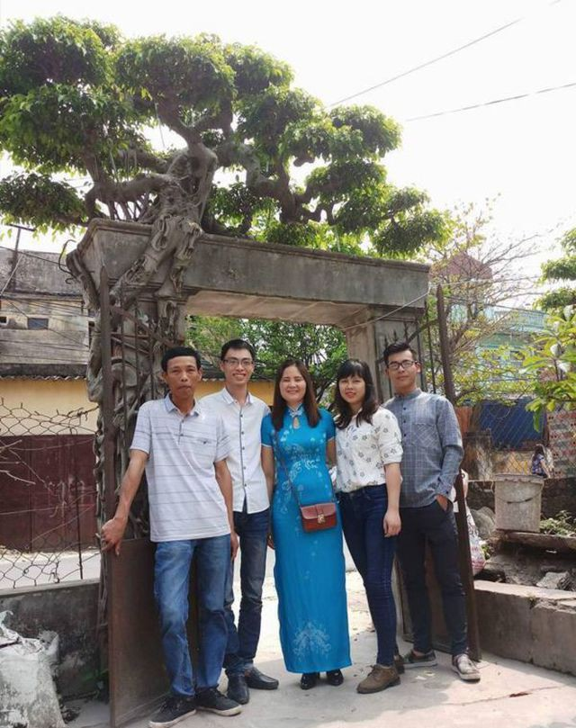 Cây sanh đã gắn bó lâu đời với gia đình ông Hoàng Văn Vinh (ngoài cùng bên trái). Ảnh: Khắc Đạt Hoàng