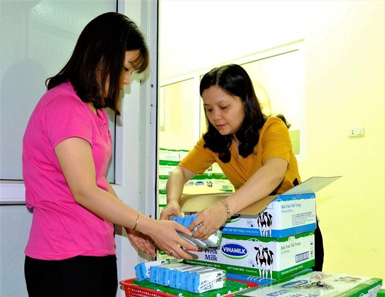 Các cô giáo chuẩn bị sữa cho các em học sinh trước giờ uống sữa học đường tại một trường mầm non ở Hà Nội.
