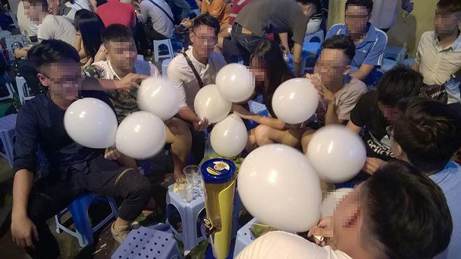 Một nhóm bạn trẻ cùng sử dụng bóng cười tại khu phố Tạ Hiện, Hà Nội. Ảnh: T.P