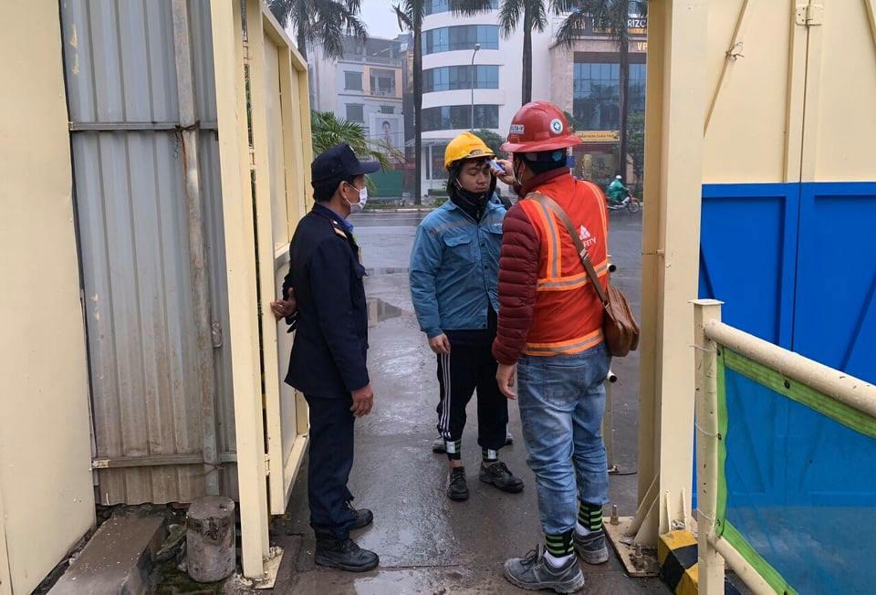 Đo thân nhiệt, phát khẩu trang cho công nhân khi vào công trường xây dựng